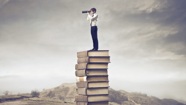 Man with binoculars standing atop a huge stack of books