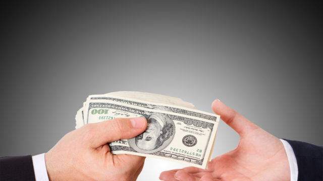 A man's hand passing money to another man's hand