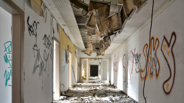 Picture of a hallway damaged by destruction and graffiti
