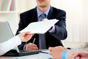 A person handing a man in a suit some documents