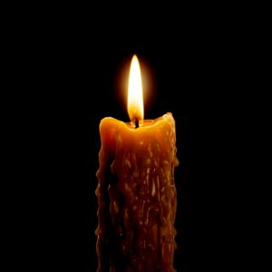 Close up view of the candle cutting through the darkness.